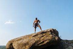 Portrait of strong black african american man bodybuilder with naked torso posing on the rock. Blue cloudy sky. Background Stock Photography
