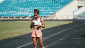 Portrait of a strong fit girl in sportswear running in the stadium. Beautiful girl runs in the stadium and listens to. Happy track running girl runner listening stock footage