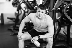 Portrait of a strong fit man in gym. Portrait of a strong fit young man exercising in a gym. Confident man looks ahead Stock Photo