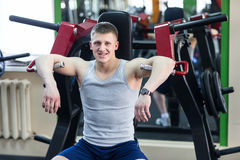 Portrait of a strong fit man in gym. Portrait of a strong fit young man exercising in a gym. Confident man looks ahead Stock Image