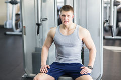 Portrait of a strong fit man in gym. Portrait of a strong fit young man exercising in a gym. Confident man looks ahead Stock Photos