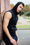Portrait of a strong handsome man in training cloth. Posing in the hood. Portrait of a strong handsome man in training cloth next the street garage. Posing in Stock Photo