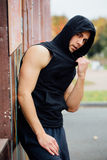 Portrait of a strong handsome man in training cloth. Posing in the hood. Royalty Free Stock Photography