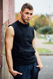 Portrait of a strong handsome man in training cloth. Posing in the hood. Stock Photos