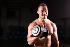 Portrait of strong healthy handsome Athletic Man Fitness Model posing with a dumbbell. Portrait of strong healthy handsome Athletic Man Fitness Model posing Stock Photo