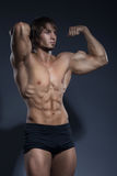 Portrait of strong healthy handsome Athletic Man Fitness Model posing near dark gray wall Stock Image