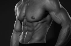 Portrait of strong healthy handsome Athletic Man Fitness Model posing near dark gray wall Royalty Free Stock Photo