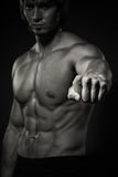 Portrait of strong healthy handsome Athletic Man Fitness Model posing near dark gray wall.  Royalty Free Stock Photo