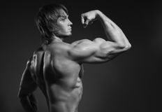 Portrait of strong healthy handsome Athletic Man Fitness Model posing near dark gray wall.  Royalty Free Stock Images
