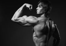 Portrait of strong healthy handsome Athletic Man Fitness Model posing near dark gray wall.  Stock Images