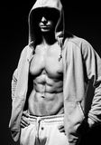 Portrait of strong healthy handsome Athletic Man Fitness Model posing near dark gray wall.  Royalty Free Stock Photos