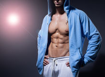 Portrait of strong healthy handsome Athletic Man Fitness Model posing near dark gray wall.  Royalty Free Stock Image