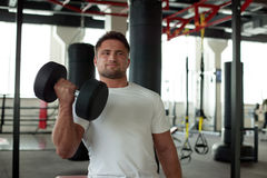 Portrait of strong man exercising with dumbbells Stock Photos