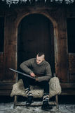 Portrait of strong viking warrior sharpening his sword, scandinavian viking cosplay, medieval warrior with steel sword sitting on. Wolf pelt in winter woods royalty free stock photography
