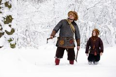 Portrait strong viking warrior winter woods battle scandinavian traditional clothing lumberjack chain mail leather spear deep fore. Father and son Vikings in a Royalty Free Stock Photography