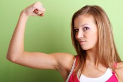 Portrait of a strong woman. Portrait of a young sporty woman is flexing her muscle Royalty Free Stock Photo