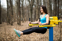Portrait of strong young woman hanging on wall bars with her legs up. Fitness woman performing hanging leg raises on outdoor in pa stock photography