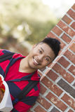 Portrait of a student. A smiling male student outdoors holding a book Stock Photography