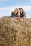 Portrait of student friends lying on big round straw bale Stock Photography