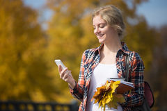 Portrait of student girl outsides, mobile phone in one hand Stock Images