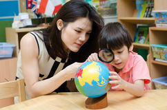 Portrait student looking at globe while listening to teacher Stock Images