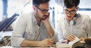 Portrait of students studying in bookstore together Stock Images
