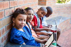 Portrait of students using digital tablet and laptop at corridor. Portrait of students using digital tablet and laptop while sitting at school corridor Stock Photography