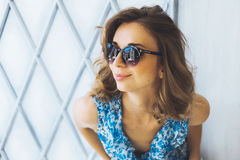 Portrait in studio beautiful young curly girl in sunglasses, short denim shorts and a blue blouse, girl posing Stock Images