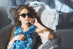Portrait in studio beautiful young curly girl in sunglasses, short denim shorts and a blue blouse, girl posing Royalty Free Stock Photo