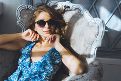 Portrait in studio beautiful young curly girl in sunglasses, short denim shorts and a blue blouse, girl posing Stock Image