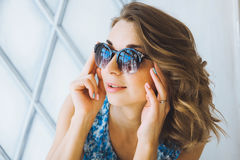 Portrait in studio beautiful young curly girl in sunglasses, short denim shorts and a blue blouse, girl posing Stock Photo