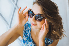 Portrait in studio beautiful young curly girl in sunglasses, short denim shorts and a blue blouse, girl posing Royalty Free Stock Photography