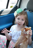 Portrait of a stunned girl eating a chocolate in the car Royalty Free Stock Images