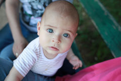 Portrait of a stunned look baby boy with gorgeous blue eyes being held by his mother Royalty Free Stock Image