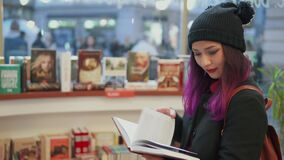 Portrait of stunning asian woman with bright red lips and purple hair reading a book in a bookstore. Millenials