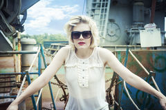 Portrait of stunning blonde with red lipstick and sunglasses on the background of the ship Royalty Free Stock Photos