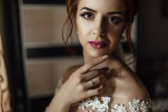 Beautiful brunette stylish bride getting ready in the morning in stock photo