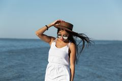 Portrait of stunning dark-haired girl in white dress, sunglasses and brown hat near the sea on a sunny day. stock images