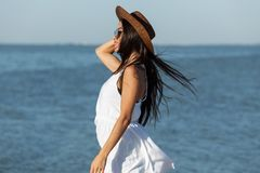 Portrait of stunning dark-haired girl in white dress, sunglasses and brown hat near the sea on a sunny windy day. royalty free stock photography