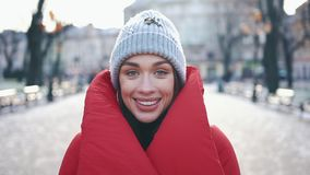 Portrait of a stunning girl in grey hat and red coat smiling while she stands on the street before Christmas decorations