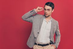 Portrait of stunning, virile, harsh, modern man holding hand in. Pocket of pants and eyelet of glasses on his face, looking to the side, standing over red Royalty Free Stock Photos