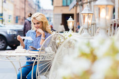 Portrait of stunning woman with luxury blonde hair reading something while sitting in sidewalk cafe during recreation time, Royalty Free Stock Image