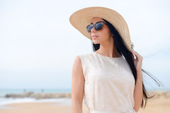 Portrait of stunningly beautiful young woman in a white dress and sunglasses. Stock Photo