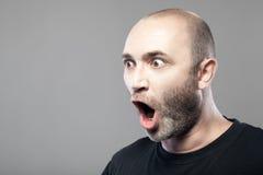 Portrait stupéfait d'homme d'isolement sur le fond gris Photographie stock libre de droits