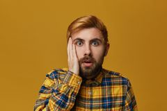 Portrait of stupefied bearded male, with dyed blond gold hair keeps mouth widely opened, wonders about something. Isolated over yellow background Royalty Free Stock Image