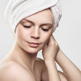 Portrait of a styled professional model. Topic: health, beauty, fashion. A girl with a towel on her head, with bare shoulders, lowered eyes with long eyelashes royalty free stock photos