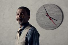 Portrait of stylish african american man. In waistcoat with clock on wall royalty free stock photos
