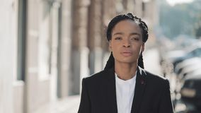 Portrait of stylish afro business woman standing on the old street background. She looking at the camera. Black Stylish stock footage