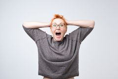 Portrait of stylish, aged, charming, surprised, shocked woman with red hairstyle holding hands on head. With wide open eyes. I can not belive these fortune stock photos