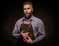 Portrait of stylish barber with beard and professional tools  on a dark  background. Portrait of stylish barber with beard and professional tools  on a dark Stock Photo